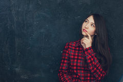 La belle fille se tient près du mur Photo libre de droits