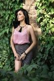 La belle fille se tient près du mur Photographie stock