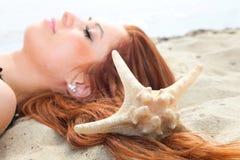 La belle fille se trouve sur la côte avec des vacances de nature de coquilles Photo libre de droits