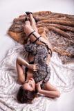 La belle fille se trouve sur une couverture blanche et des oreillers avec des modèles Images libres de droits