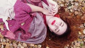 La belle fille sensuelle avec des mensonges rouges de cheveux au-dessus des feuilles sèches tient une cendre de montagne dans la  Photo libre de droits