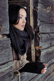 La belle fille seule regarde la fenêtre de la maison dans un jour d'hiver givré d'espace libre d'hiver Image stock