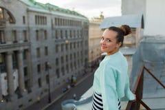 La belle fille seule se tient sur le toit de la maison dans la vieux ville et rêves Photos stock