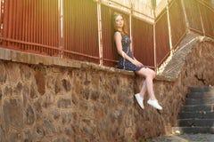 La belle fille sexy avec des cheveux et le maquillage dans la robe s'assied sur la pierre Image libre de droits