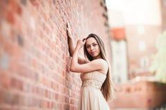 La belle fille sexy avec la longue forme parfaite de cheveux et de robe a bronzé le corps possing près du mur Images stock