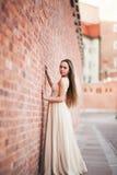 La belle fille sexy avec la longue forme parfaite de cheveux et de robe a bronzé le corps possing près du mur Photos libres de droits