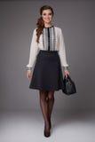 La belle fille sexy dans les affaires vêtx dans une jupe courte au chemisier de rose de genou avec des talons hauts Image stock