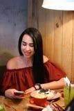 La belle fille souriant, prises dans des mains téléphonent et des utilisations il, conduc Images libres de droits