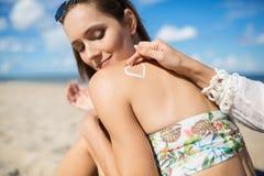 La belle fille sur la plage et son ami appliquant le bronzage l'huilent dessus Photos libres de droits