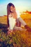 La belle fille sur le pré se reposant sur la cueillette d'herbe fleurit photo stock