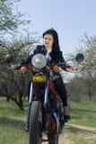 La belle fille sur une moto Images stock