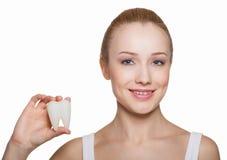 La belle fille tient le modèle de dent dans une main Images stock