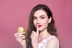 La belle fille tient un macaron et les expositions se connecte un fond rose Photo libre de droits