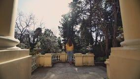 La belle fille va au balcon antique avec la vue sur le jardin vert un jour ensoleillé chaud banque de vidéos
