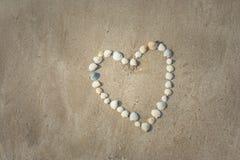 La belle forme blanche de coeur est faite à partir de la diverse coquille qu'elle a placée sur la plage de sable Images stock