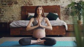 La belle future maman pratique le yoga de hatha en appartement moderne se reposant sur le tapis et les vêtements de sport de mate clips vidéos