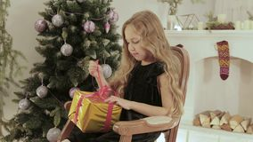 La belle, gaie fille ouvre son cadeau sur le fond de l'arbre de Noël banque de vidéos