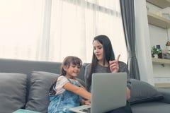 La belle giovani mamma e figlia stanno utilizzando il taccuino sul sofà alla h fotografia stock libera da diritti
