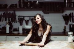 La belle hôtesse de sourire faisant cuire, malaxent la pâte Photos stock