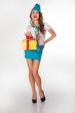 La belle hôtesse tient le cadeau sur un fond blanc Photographie stock libre de droits
