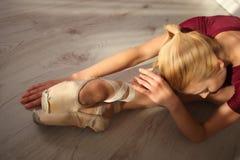 La belle jeune ballerine gracieuse dans des chaussures de pointe au plancher en bois blanc fait l'étirage de jambe de ballet Photo libre de droits