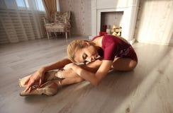 La belle jeune ballerine gracieuse dans des chaussures de pointe sur le plancher en bois fait l'étirage de jambe de ballet lense  Photo stock