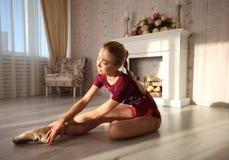 La belle jeune ballerine gracieuse dans des chaussures de pointe sur le plancher en bois fait la jambe de ballet étirant la lumiè Photos stock