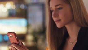 La belle jeune blonde dans la veste noire s'assied dans la boutique de café Elle est concentrée sur le service de mini-messages  clips vidéos