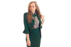 La belle jeune blonde dans un costume vert a abaissé ses yeux vers le bas et posant pour l'appareil-photo Images stock