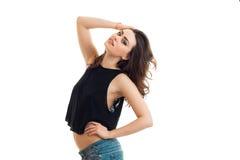 La belle jeune brune étonnante pose la tête de recourbement et garde une main du côté Image stock