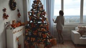 La belle jeune brune dans un chandail chaud marche à une fenêtre près d'un arbre de Noël et regarde la rue banque de vidéos