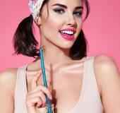 La belle jeune brune avec la coiffure et la coiffe lumineuse de maquillage sourient, portant une exploitation furtive de mai Images stock