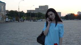 La belle jeune dame dans une robe douce va chercher égaliser la ville et dit au téléphone banque de vidéos