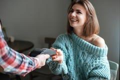 La belle jeune dame paye son ordre avec la carte de débit Photos libres de droits