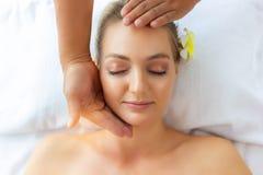 La belle jeune dame se sentent détente, bonheur et soulagement d'effort quand massage de massager sur son beau visage au salon de image libre de droits