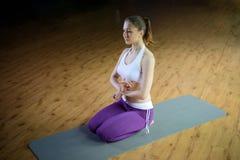 La belle jeune femelle sportive font le virasana de yoga photographie stock