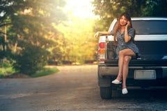 La belle jeune femme à l'aide de son téléphone portable s'asseyent sur la voiture Photo libre de droits