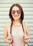 La belle jeune femme à la mode de brune se tire pour des tresses sur le mur de fond Été photos stock