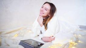 La belle jeune femme apprécie la chaleur et le confort, sourit et regarde l'appareil-photo, se trouvant sur le plancher couvert p banque de vidéos