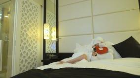 La belle jeune femme après douche avec une serviette sur sa tête dans le manteau blanc s'étend sur le grand lit avec l'ours de no banque de vidéos