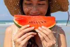 La belle jeune femme asiatique regarde la pastèque pour manger dans la saison d'été la belle plage par temps chaud qui rendent be images stock