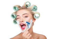 La belle jeune femme au foyer avec des bigoudis fait Photographie stock libre de droits