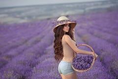La belle jeune femme avec dans le chapeau en osier posant dans le pourpre laven photographie stock