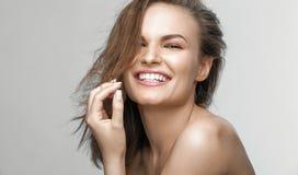 La belle jeune femme avec de longs cheveux bruns et le blanc sourient Image stock