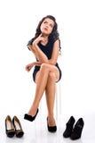 La belle jeune femme avec de longs cheveux choisit des chaussures photographie stock libre de droits