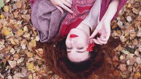 La belle jeune femme avec des mensonges rouges de cheveux au-dessus des feuilles sèches tient une cendre de montagne dans la forê Photos stock