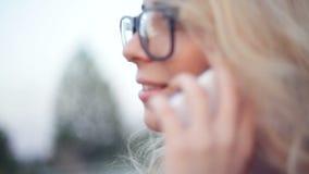 La belle jeune femme avec des verres parle au téléphone banque de vidéos