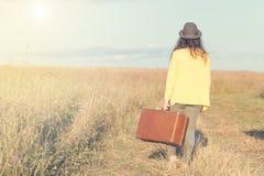 La belle jeune femme avec le chapeau noir porte la valise brune de vintage dans la route de champ pendant le coucher du soleil d' images stock