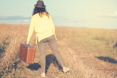 La belle jeune femme avec le chapeau noir porte la valise brune de vintage dans la route de champ pendant le coucher du soleil d' photo libre de droits