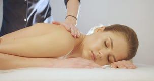 La belle jeune femme avec le maquillage naturel se repose tout en ayant le massage dans le salon professionnel longueur 4k banque de vidéos